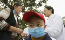 A Chinese boy diagnosed with leukaemia wears a mask as he listens to discussion between his mother and a cancer specialist on November 2, 2004 at Longshi, Chongqing, China.