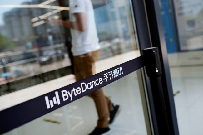 FILE PHOTO: Man walks by a logo of Bytedance, which owns short video app TikTok, at its office in Beijing