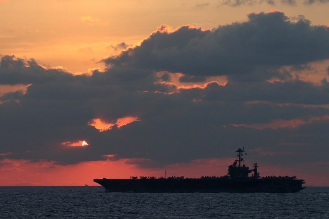The U.S. Navy aircraft carrier USS John C. Stennis transits the South China Sea at sunset