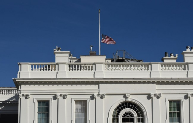 The US flag flies at half-mast above the White House